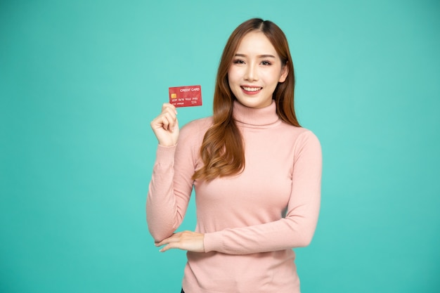 Asian woman smiling and showing credit card.