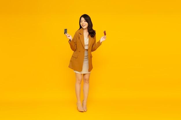 Asian woman smiling and showing credit cardon yellow wall.