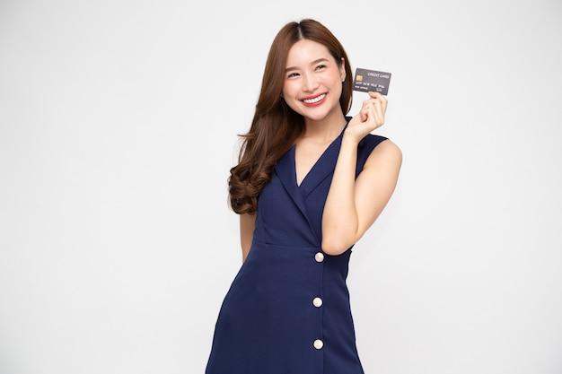 Азиатская женщина улыбается, показывая представление кредитной карты для совершения платежа или оплаты онлайн-бизнеса