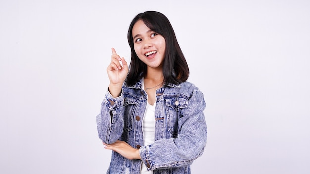 Asian woman smiling wearing jeans jacket and thinking some idea with isolated white surface
