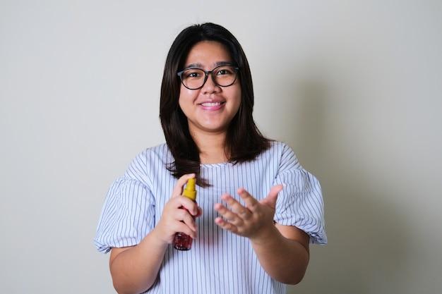 손에 손 소독제 스프레이를 사용하면서 웃고 있는 아시아 여성