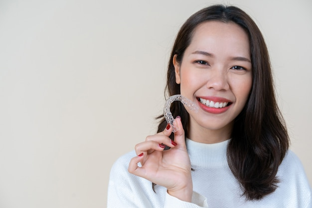 Asian woman smiling with hand holding dental aligner retainer