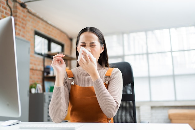 Asian woman sneezes. she uses a tissue to cover her mouth and she is working at home.