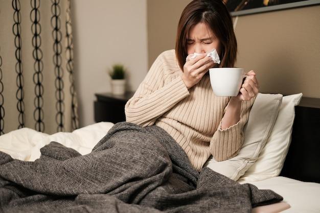 Азиатская женщина чихает и самкарантинует дома. инфекция от микробов, бактерий, covid19, короны, сарс, вируса гриппа. концепция болезни и болезни