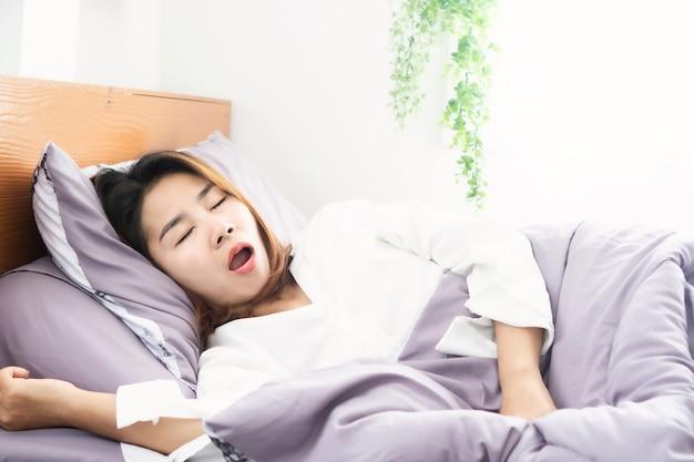 ベッドで寝ている間にいびきをかくと口を開けるアジアの女性