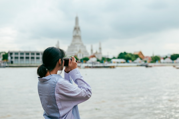 Asian woman solo travelers and take photo ancient pagoda buildings