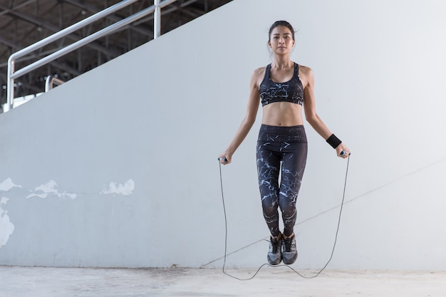 Asian woman sports girl doing exercises with jumping rope.