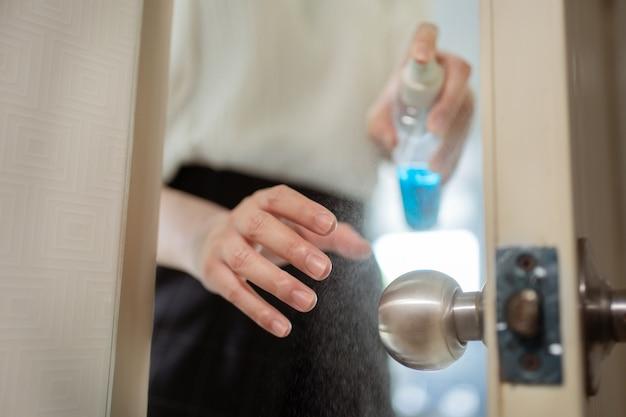 Азиатская женщина распыляется алкоголь на дверную ручку. убить микробы и вирусы