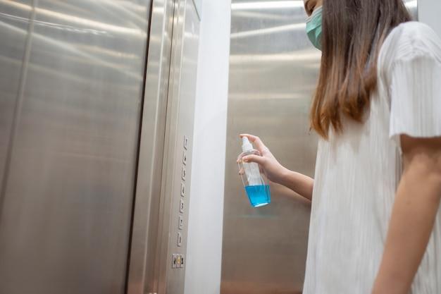 엘리베이터 버튼 킬 세균과 바이러스를 입고 알코올을 분사 아시아 여자