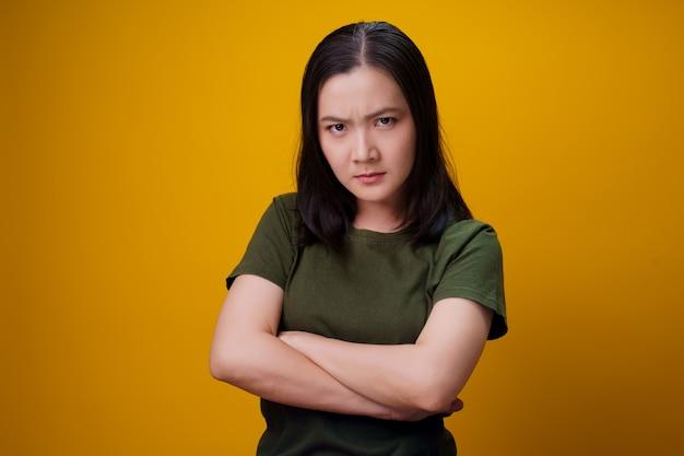 立っていると怒っているアジアの女性は黄色の壁に孤立しました。