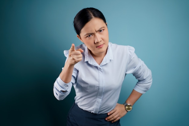 Asian woman standing and angry isolated on blue.