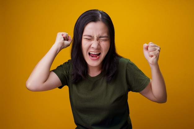 Asian woman standing and angry isolated over yellow wall.