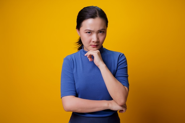 Asian woman standing and angry over yellow.