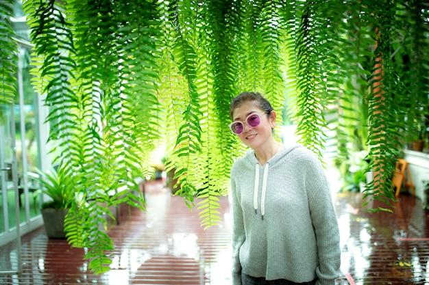 緑のシダと家のテラスに立っているアジアの女性の葉の背景