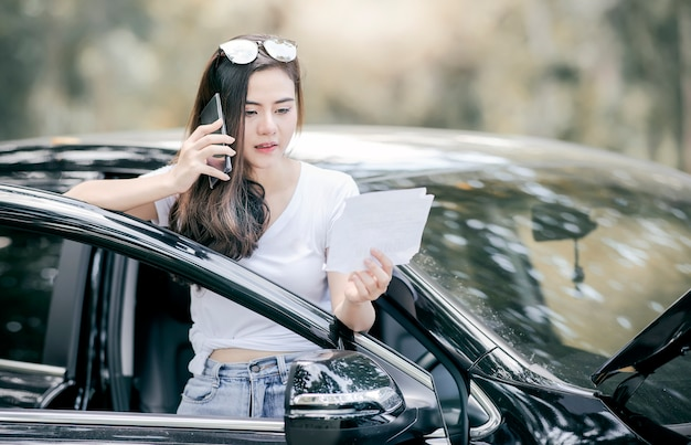 Asian woman standing by broken down car and using smartphone for assistance.