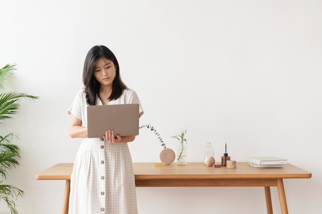Asian woman standing by the wooden table using a laptop