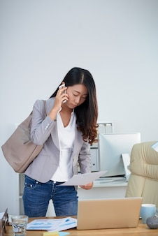 Asian woman standing at desk in office with bag on shoulder and talking on mobile phone