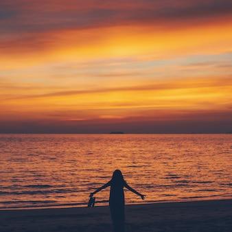 Азиатская женщина, стоящая на пляже у моря в утреннем небе с фоном восхода солнца.