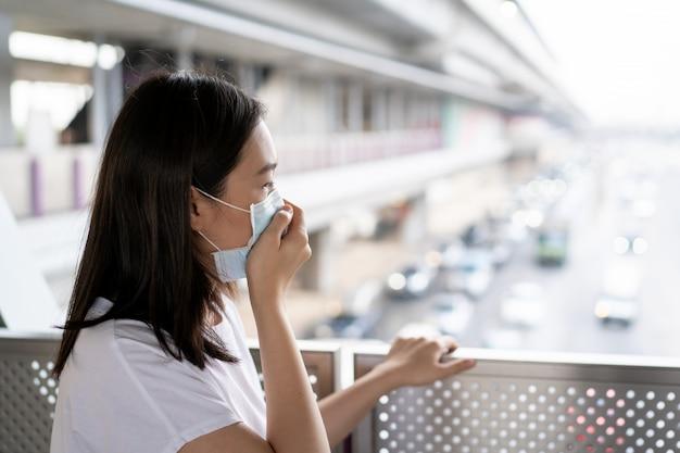 Pm2.5のほこりで完全に街の橋の上に立っているアジアの女性。 covid19ウイルスから身を守るために防護マスクを身に着けている女性。 covid-19疾患に関する女性の懸念。コロナウイルスの危機。