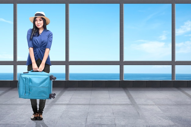 바다 전망을 배경으로 리조트에 여행 가방을 들고 서 있는 아시아 여성