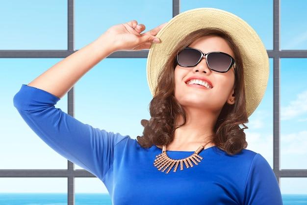 바다 전망을 배경으로 리조트에 모자와 선글라스를 들고 서 있는 아시아 여성