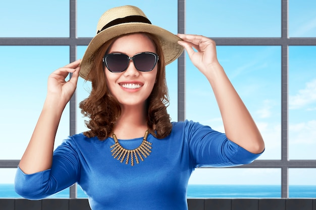 Asian woman standing with hat and sunglasses on the resort with ocean view background