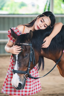 Asian woman standing with her eyes closed and lovingly hugging the horse.