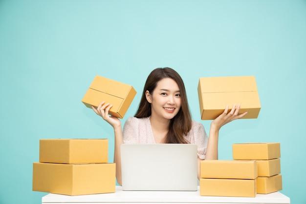Азиатская женщина запускает малый бизнес-фрилансер, держа коробку с посылкой и компьютерный ноутбук и сидя изолированно на зеленом фоне
