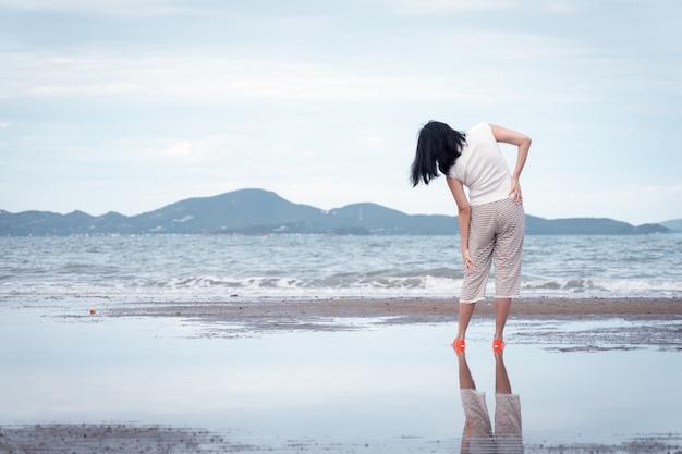 アジアの女性は体を伸ばし、ビーチで少し運動します。休日の休暇とリラックスのためのコンセプト。