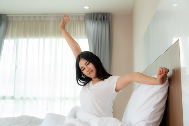 Asian woman stretching hands and body in bed after wake up in bedroom at home. concept for start new day with happiness. copyspace on the left. young happy working female life