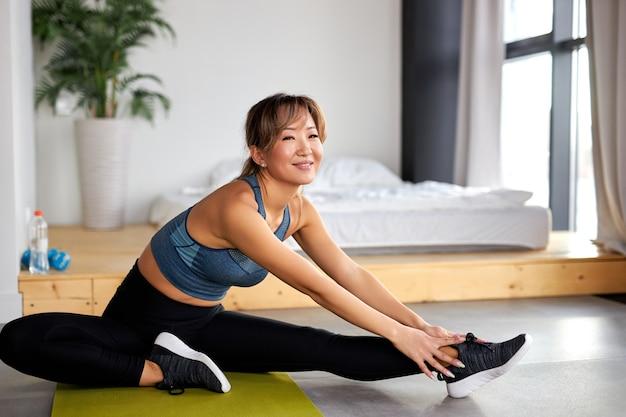 足を伸ばし、マットの上でエクササイズをしているアジアの女性、トレーニング。健康的なライフスタイルとスポーツの概念