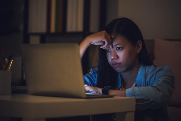 アジアの女子学生や実業家は夜遅くまで働きます。ノートパソコンやノートブックを持った暗い部屋の机に集中して眠くなる。人々の概念は一生懸命働き、燃え尽き症候群。