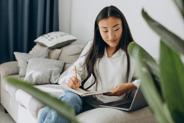 家で勉強し、ソファで読書アジアの女性