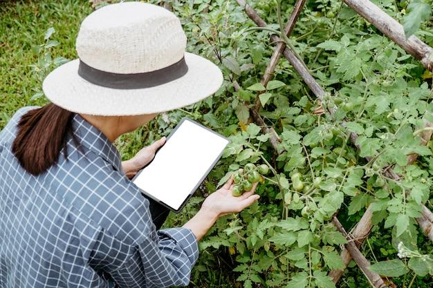 Donna asiatica che studia piante diverse con un tablet