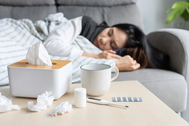 코로나19 증상으로 고통받는 아시아 여성은 집에서 자가 격리해야 합니다. 소녀는 책상 위에 티슈, 알약, 물 한 잔을 들고 소파에 누워 열이 있습니다. 감기, 독감 및 건강 문제 개념