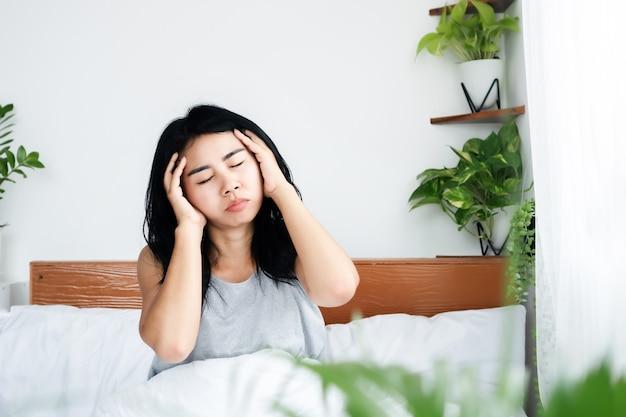 아침에 일어난 후 두통으로 고통받는 아시아 여성