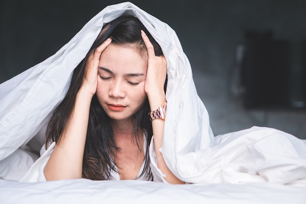 Asian woman suffering from headache in bed