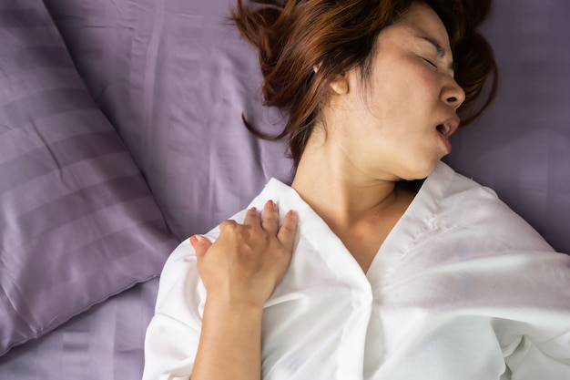 Asian woman suffering from neck sprain in bed