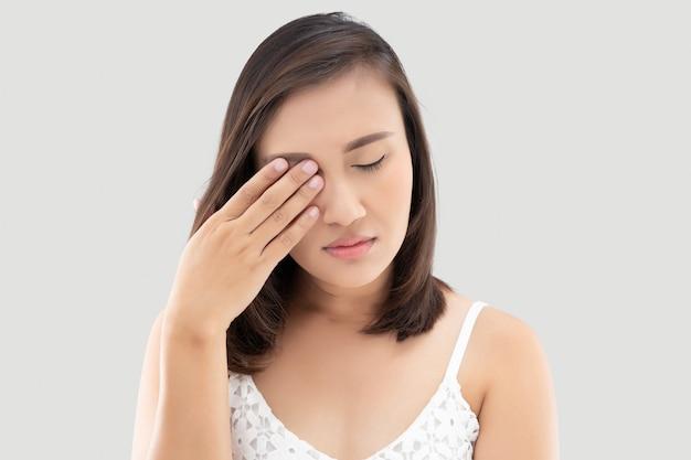 強い目の痛みに苦しんでいるアジアの女性