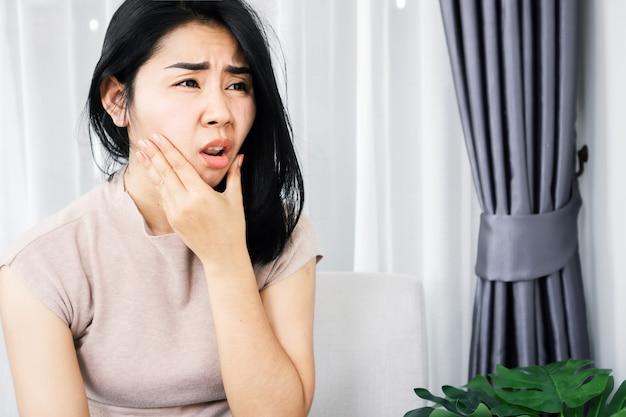 歯痛の問題に苦しんでいるアジアの女性手持ち顔の痛みを伴う歯茎