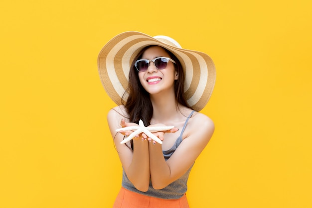 Asian woman in summer casual clothes smiling and holding starfish in hands