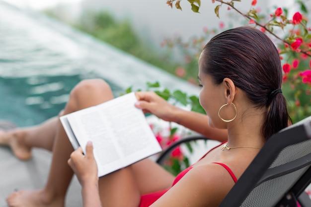 La donna asiatica in costume da bagno si rilassa in piscina sul lettino leggere il libro in villa da un albero di fiori colorati