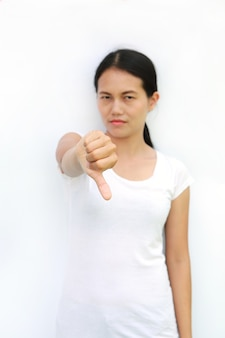 Asian woman in t-shirt showing down on white background, selected focus at her finger