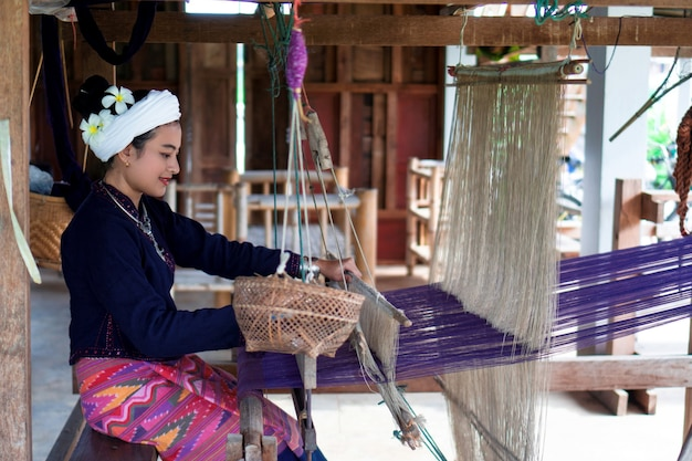 Asian woman in tai lue traditional dress (northern thailand culture) is weaving fabric with old wooden machine, ethnic working, nan culture, thailand