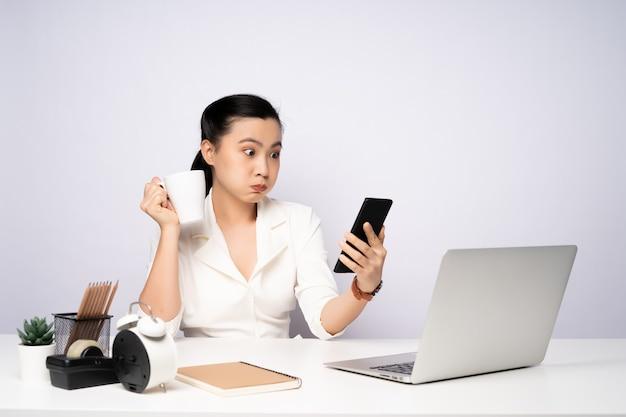 Азиатская женщина делает перерыв после работы и использования смартфона. изолированные на белом фоне.