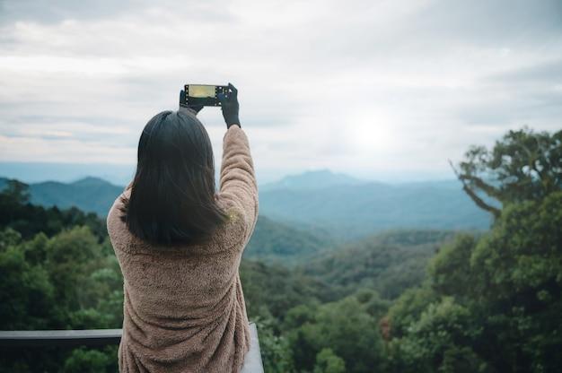 アジアの女性がタイの山でスマートフォンで写真を撮る