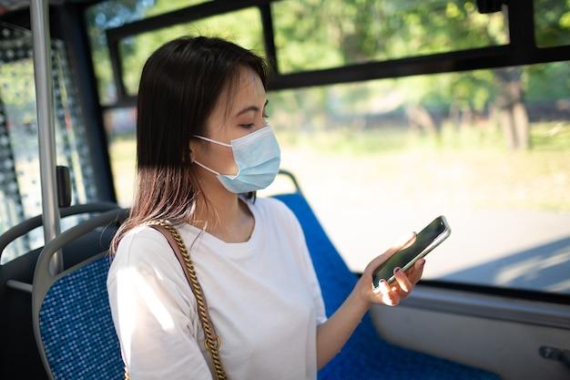 アジアの女性がフェイスマスクで公共交通機関のバスや路面電車に乗る