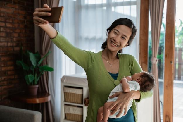 アジアの女性は小さな娘を保持するときにselfieを取る