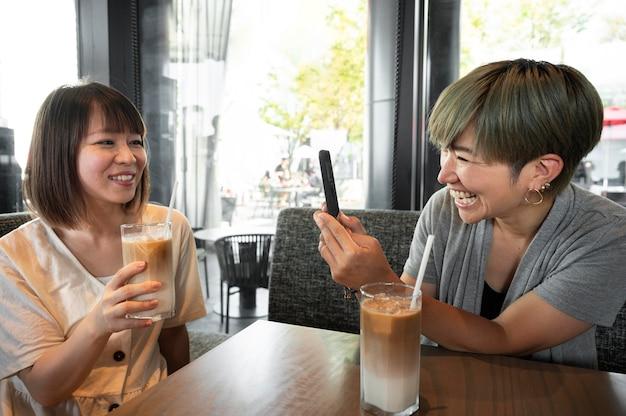 彼女の携帯電話で彼女の友人の写真を撮るアジアの女性