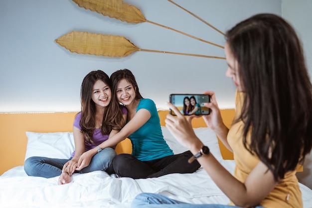 寝室で一緒にぶらぶらしながら電話を使用して彼女の友人の写真を撮るアジアの女性